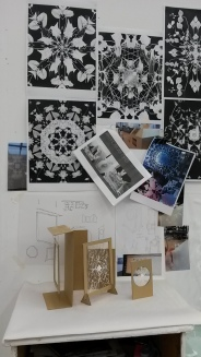 Close up of one half of the studio space showing photographs about the lasercutter.
